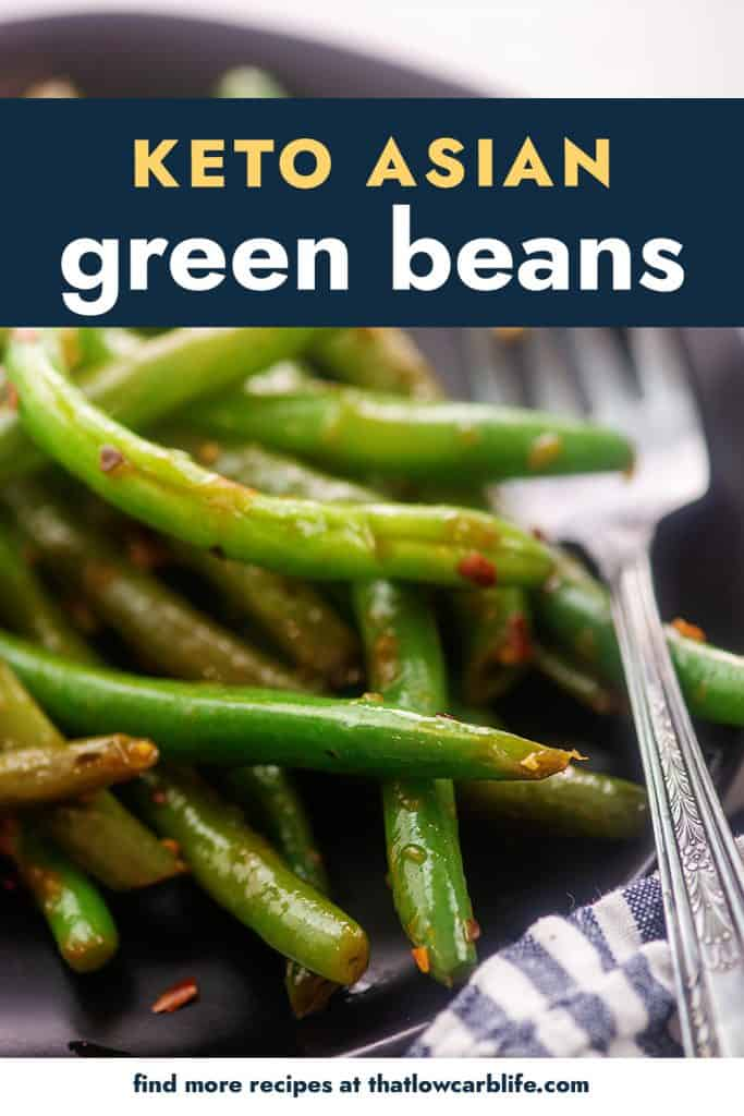 spicy green beans on black plate with fork.