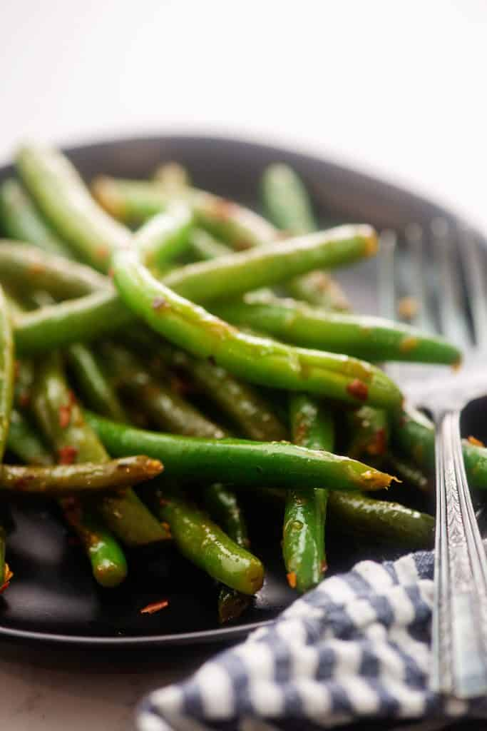 green beans on black plate with fork.