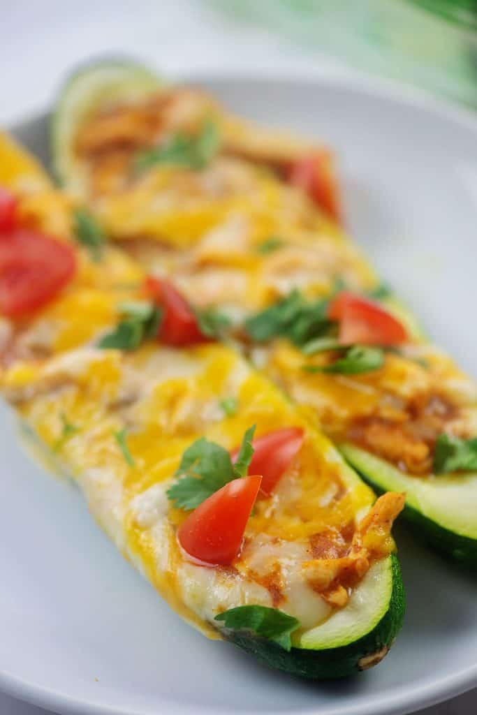 two zucchini boats on white plate topped with tomato and cilantro.