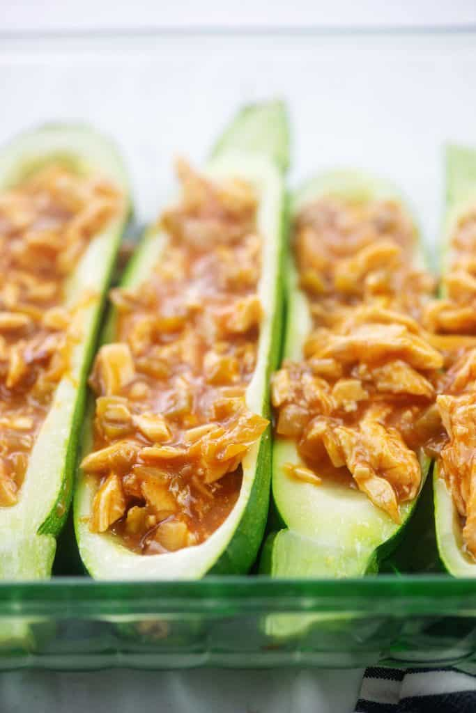 zucchini boats filled with chicken enchilada mixture in glass dish.