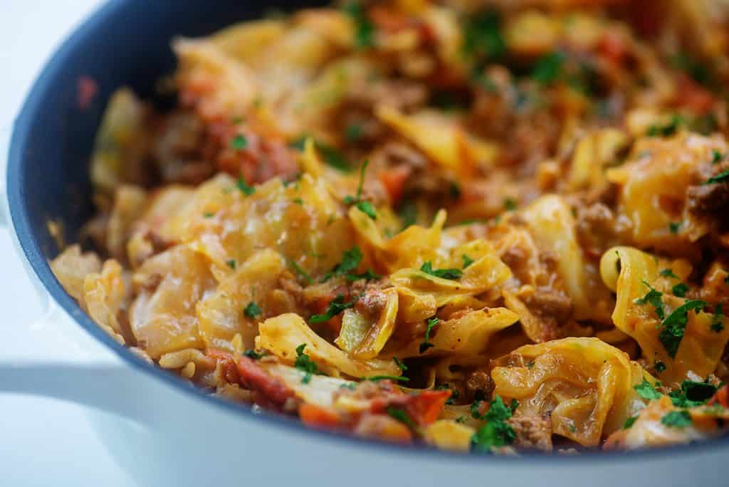 cheesy cabbage and beef in white skillet.