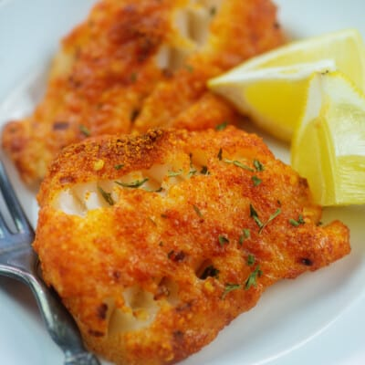 Parmesan crusted cod on white plate.
