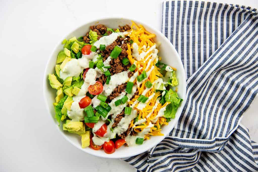 overhead view of keto taco salad in white bowl with blue napkin