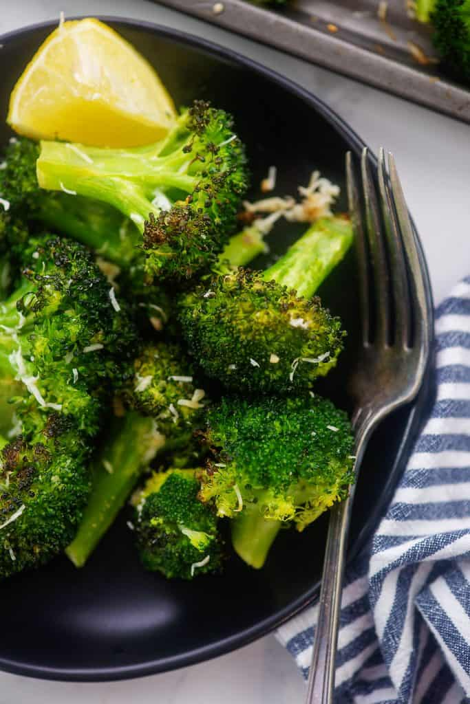 overhead view of roasted broccoli on black plate.