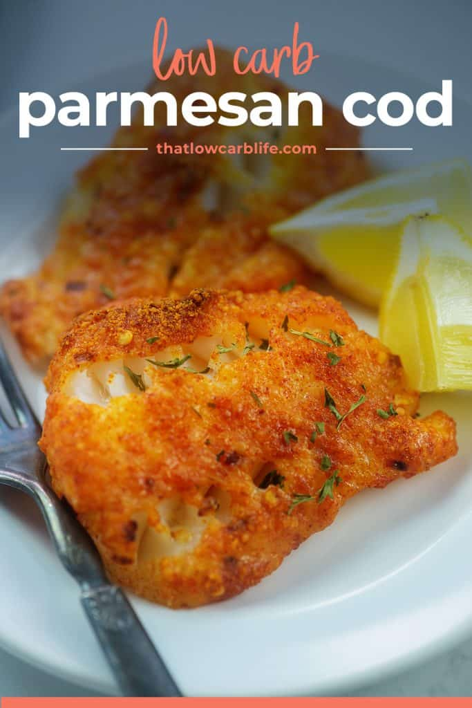 baked cod fish recipe on plate with lemon wedges.
