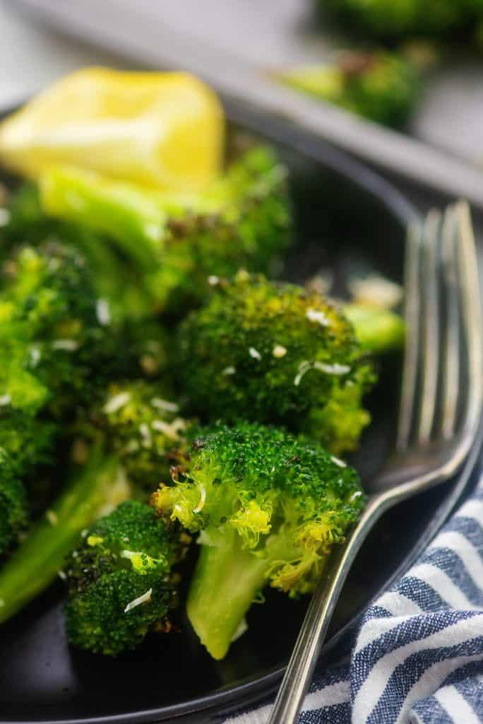 roasted broccoli on black plate.