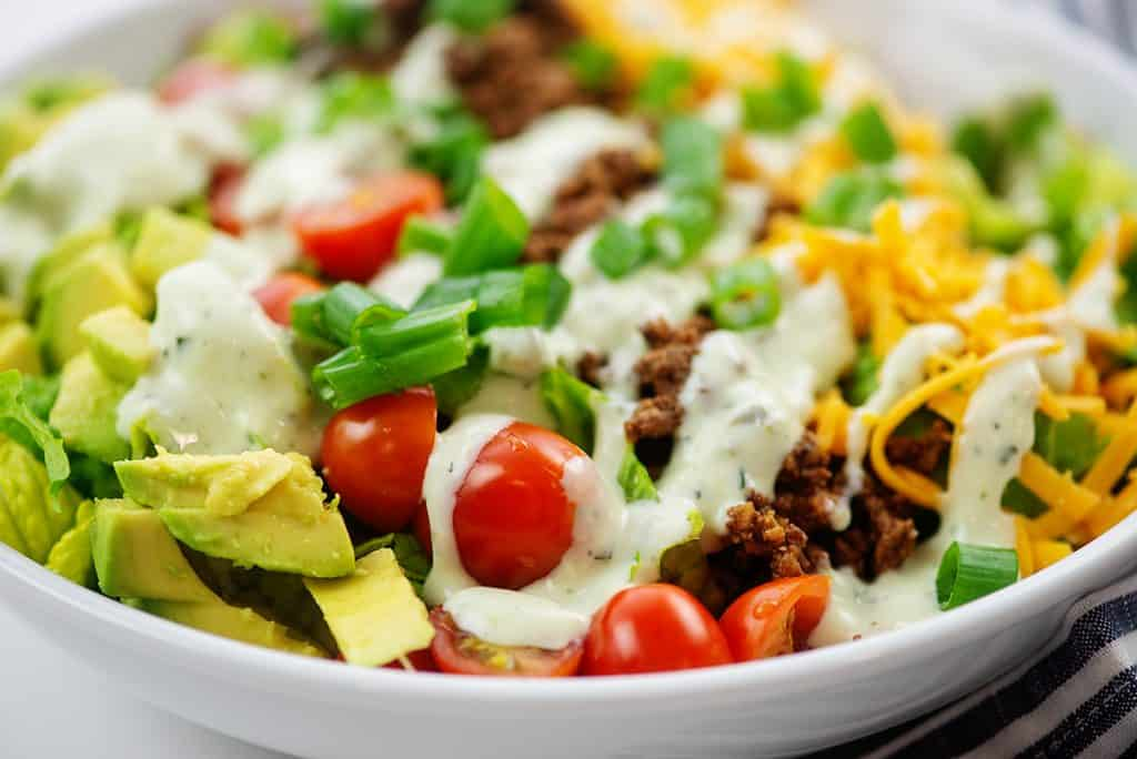 taco salad topped with avocado dressing in white salad bowl.