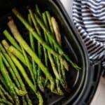 overhead view of asparagus in air fryer basket.