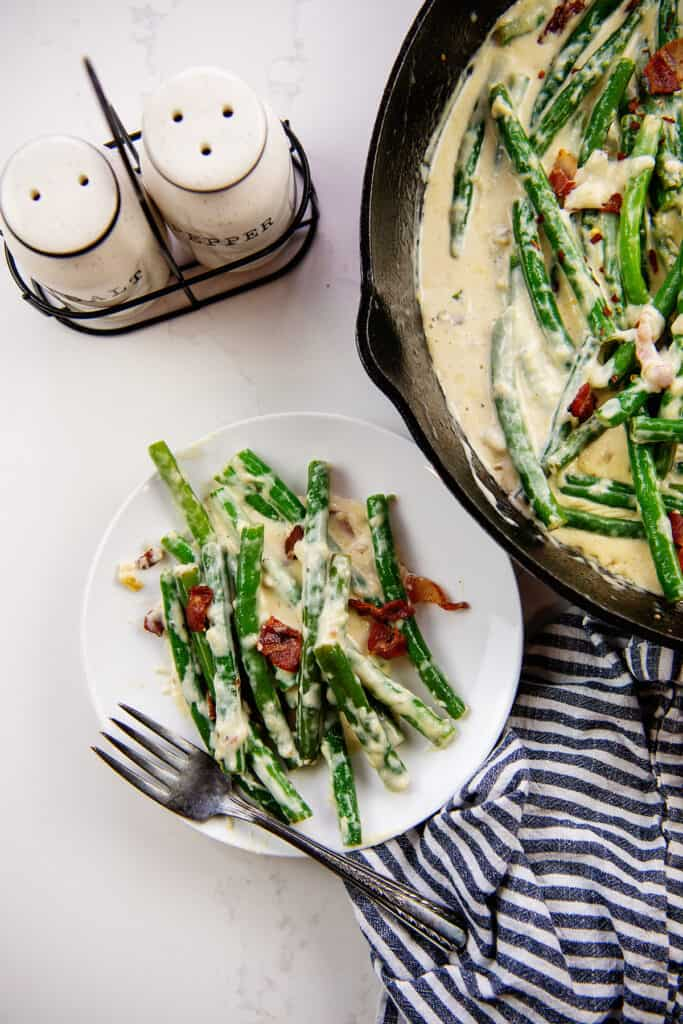 Creamy parmesan green beans on white plate next to skillet.