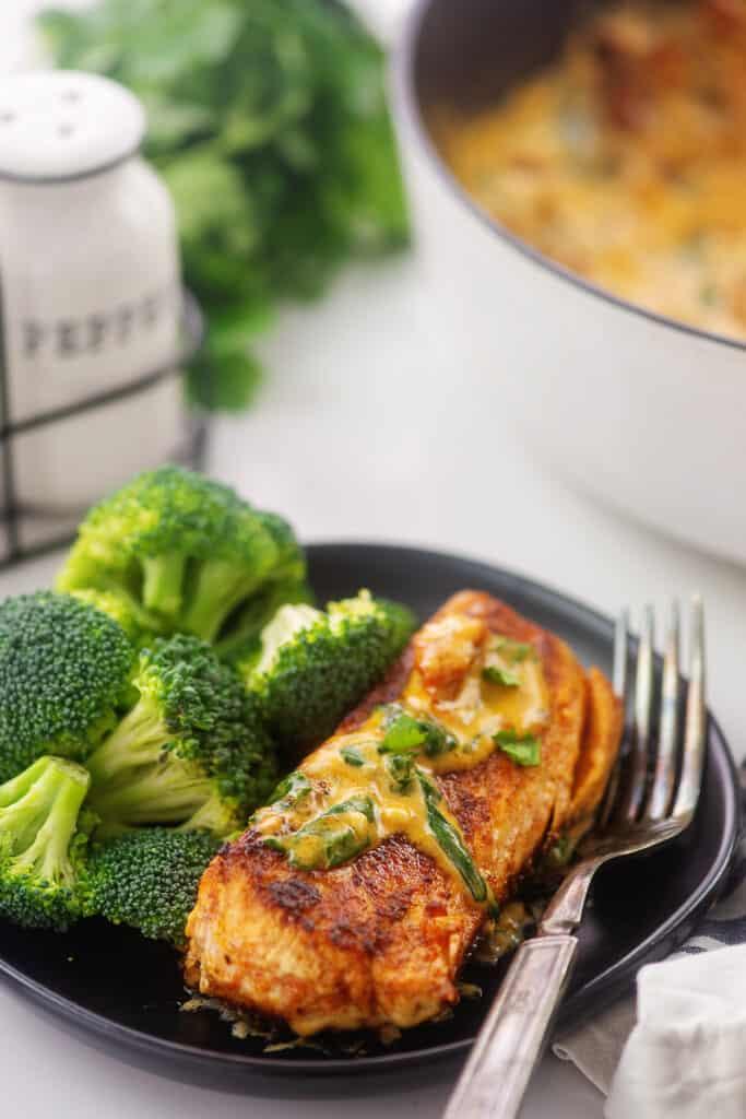 tuscan salmon recipe on black plate next to broccoli.