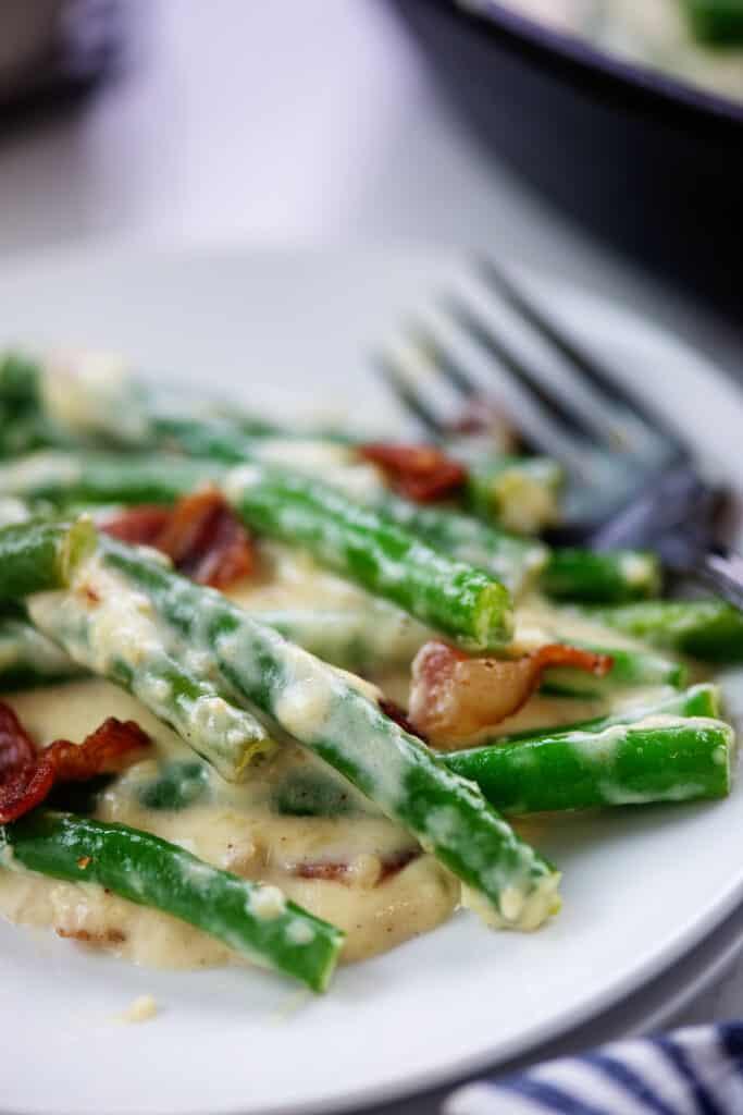 Garlic parmesan green beans on white plate.