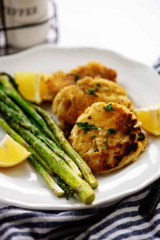 crab cakes on white plate with asparagus.