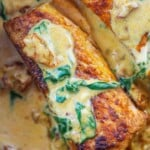 close up view of creamy Tuscan salmon in cream sauce.