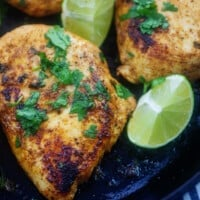 chicken breasts in black skillet with cilantro and lime.