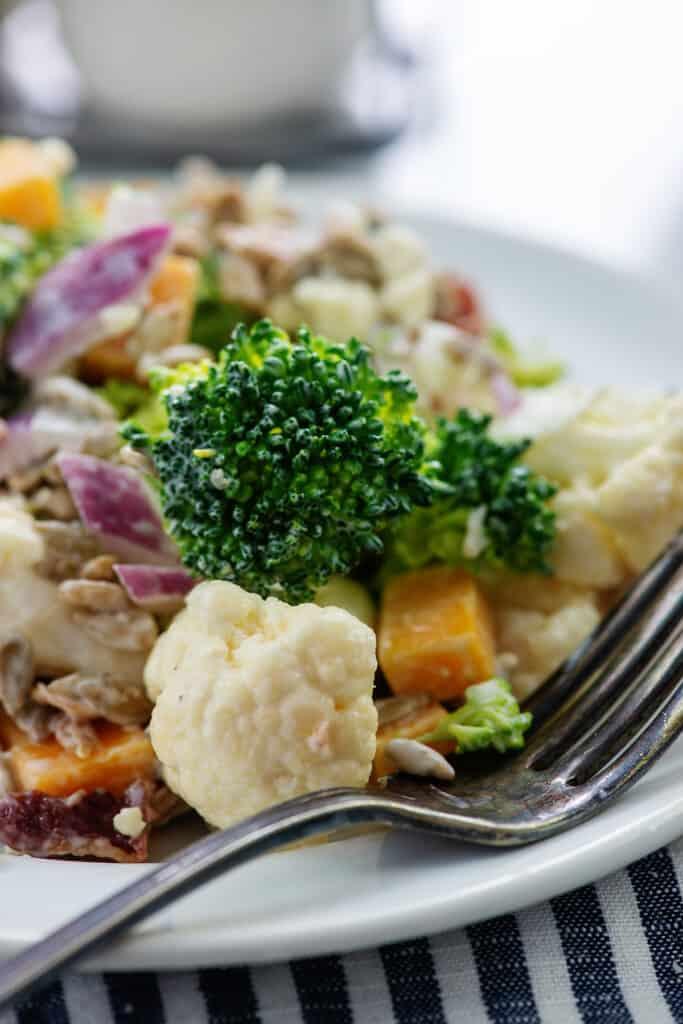 cauliflower broccoli salad on white plate with vintage fork.