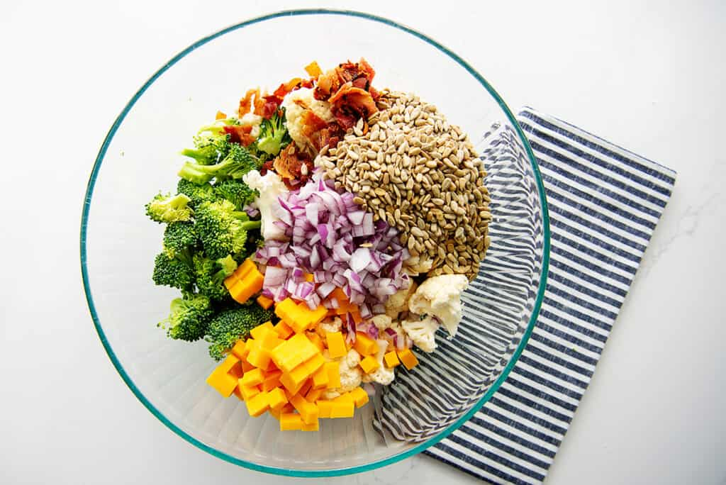 overhead view of broccoli salad ingredients in glass bowl.