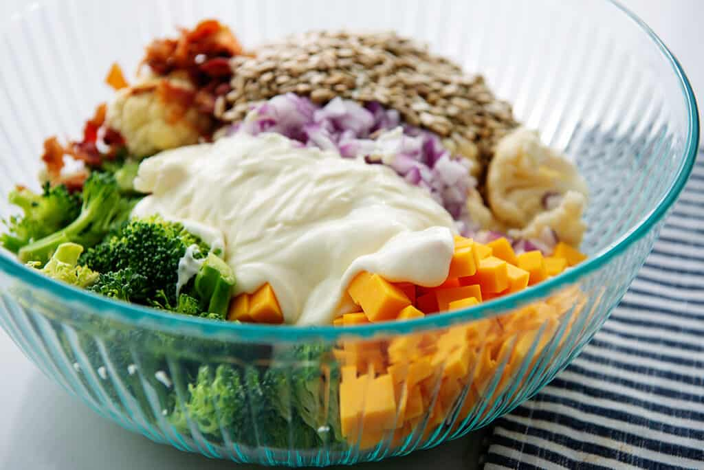 broccoli and cauliflower salad with dressing over the top.