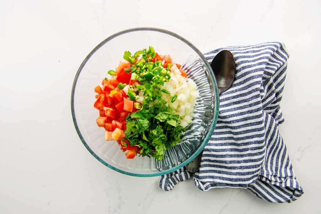 ingredients for pico de gallo in glass bowl.