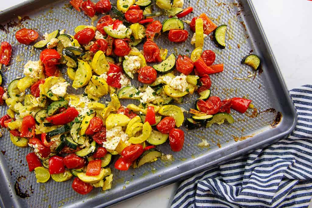 vegetables mixed with feta cheese on baking sheet.