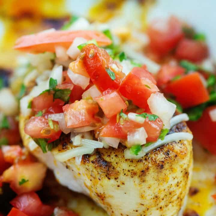 baked chicken breasts topped with salsa fresca in white baking dish.