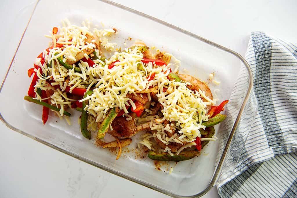 chicken in glass dish topped with vegetables and cheese.
