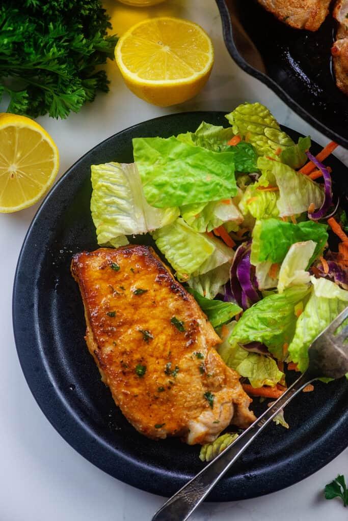 lemon garlic pork chops with salad on black dinner plate.