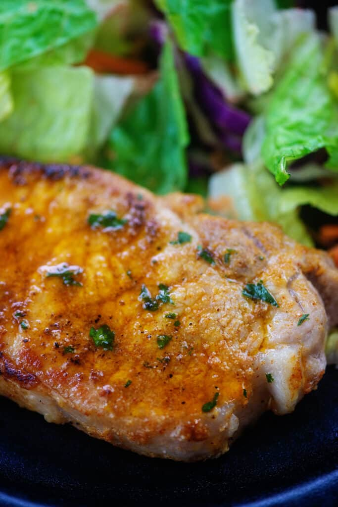 lemon garlic pork chop on plate with salad.