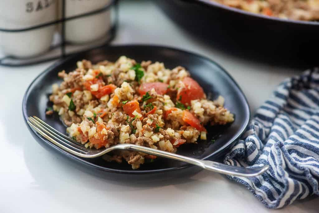 Keto cauliflower rice recipe on black plate.