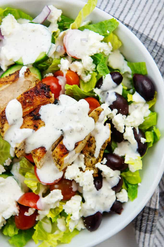 overhead view of Greek chicken salad with tzatziki dressing in white bowl.