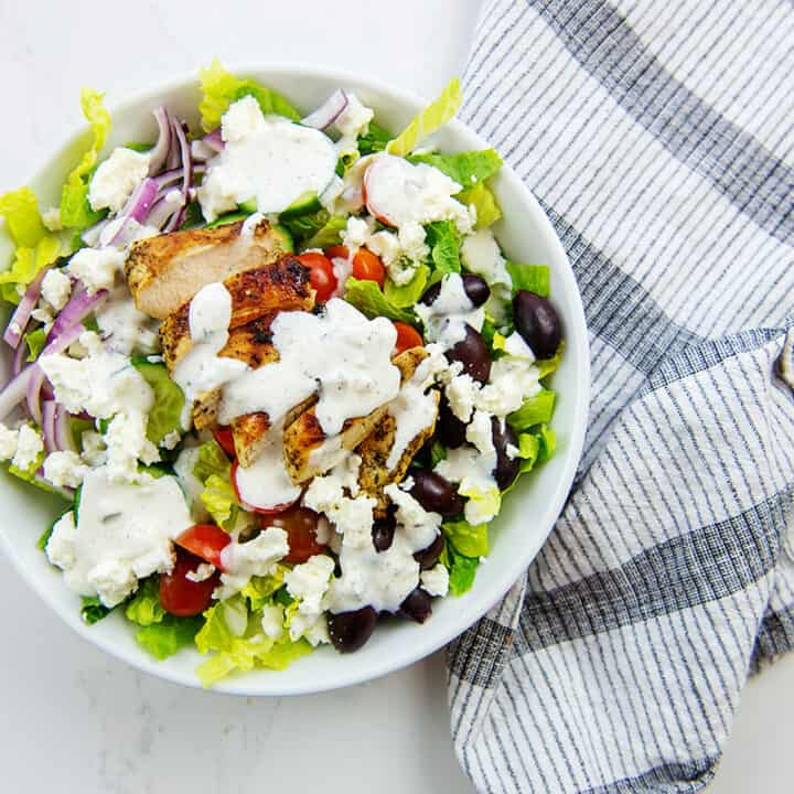 overhead view of Greek salad with chicken and tzatziki dressing in white bowl.