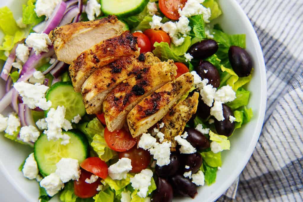 greek chicken salad recipe in white bowl.