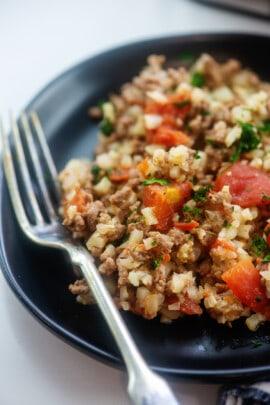 cauliflower rice and beef on black plate.