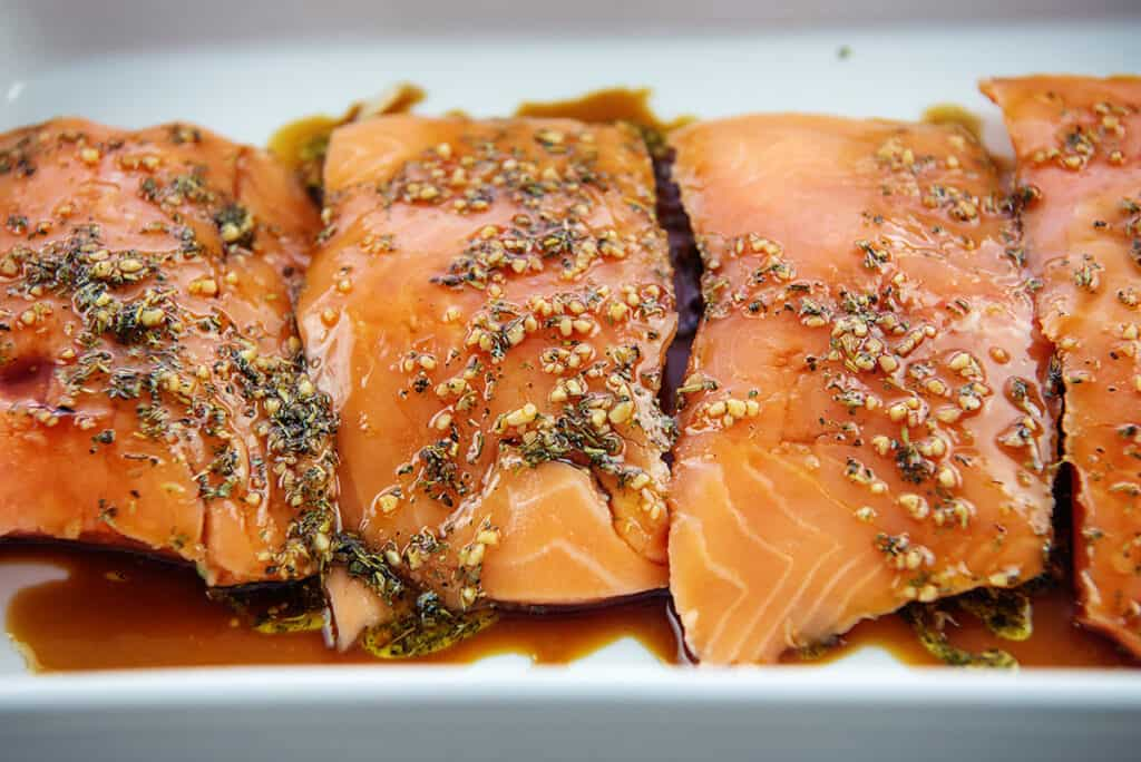 salmon in marinade in white baking dish.