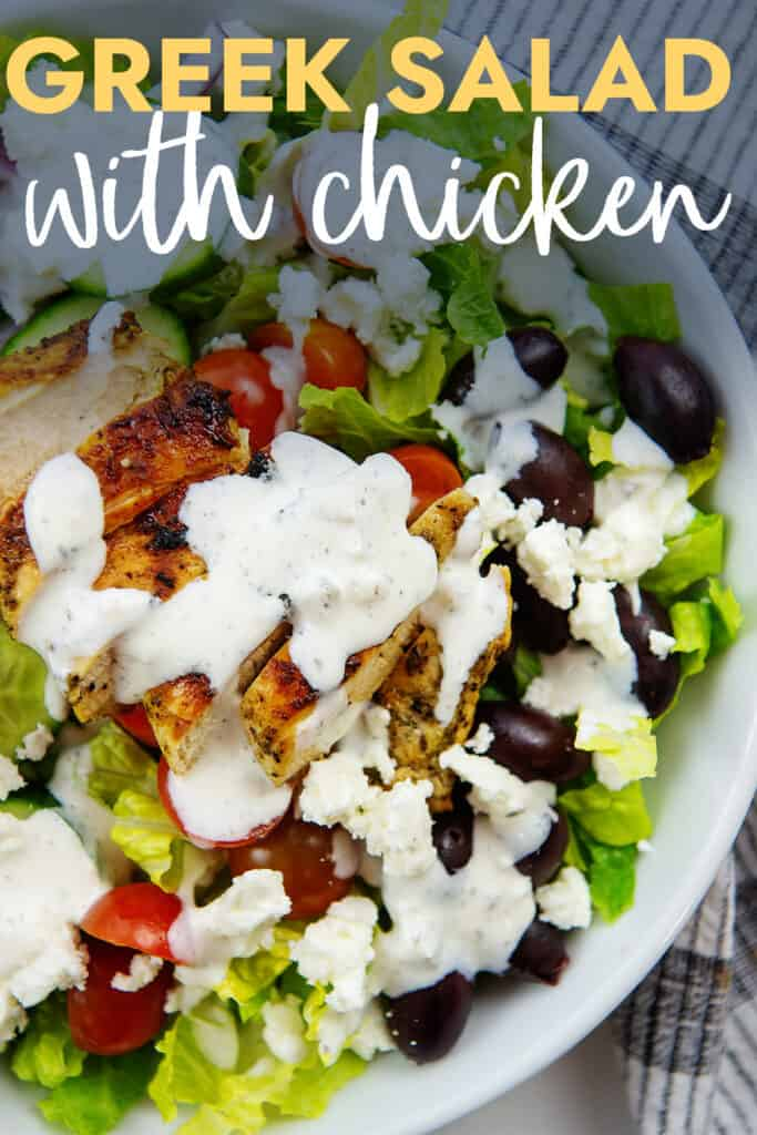 greek salad topped with chicken with text for Pinterest.
