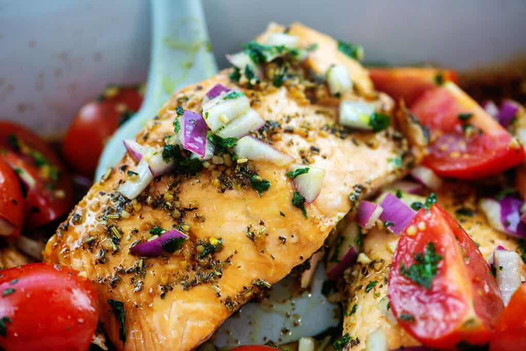 baked salmon with tomatoes and basil on top.