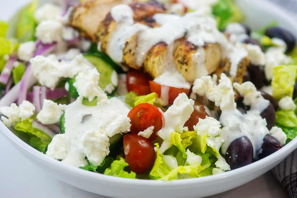 greek chicken salad in white bowl.