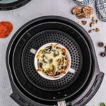 crustless pizza in air fryer basket.