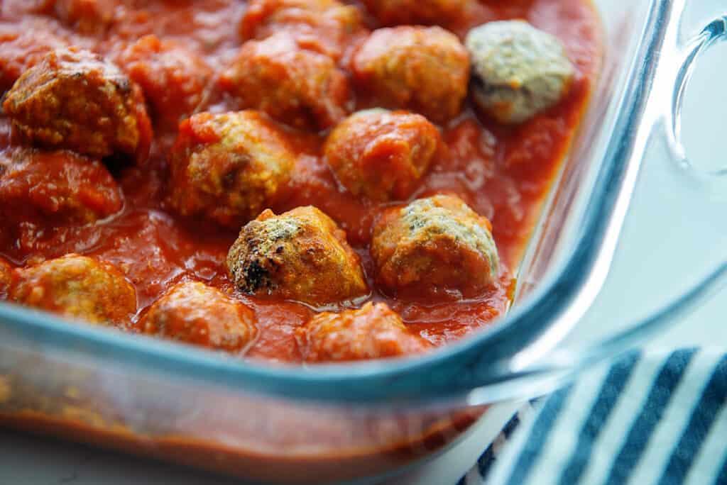 meatballs in marinara sauce in glass dish.