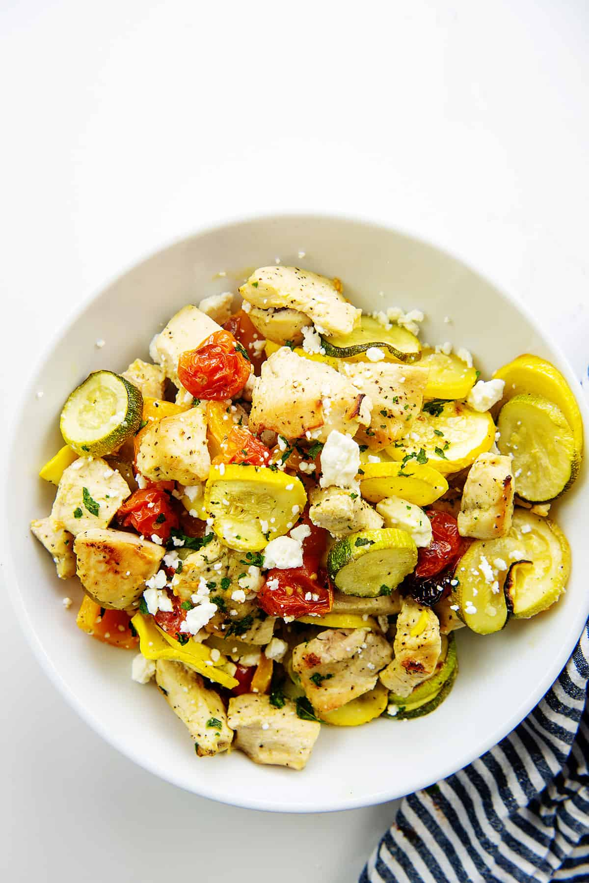 greek chicken and vegetables in white bowl.