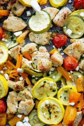 overhead view of greek chicken and vegetables on a sheet pan.