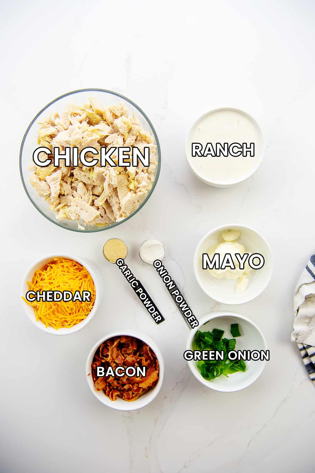 ingredients for chicken salad on white countertop.