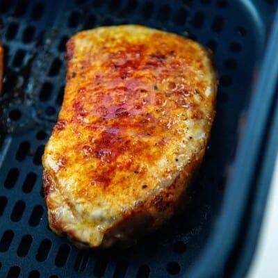 boneless pork chop in air fryer basket.