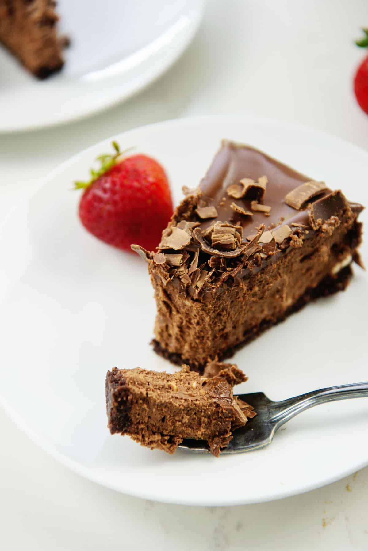 slice of chocolate cheesecake with a bite on a fork.