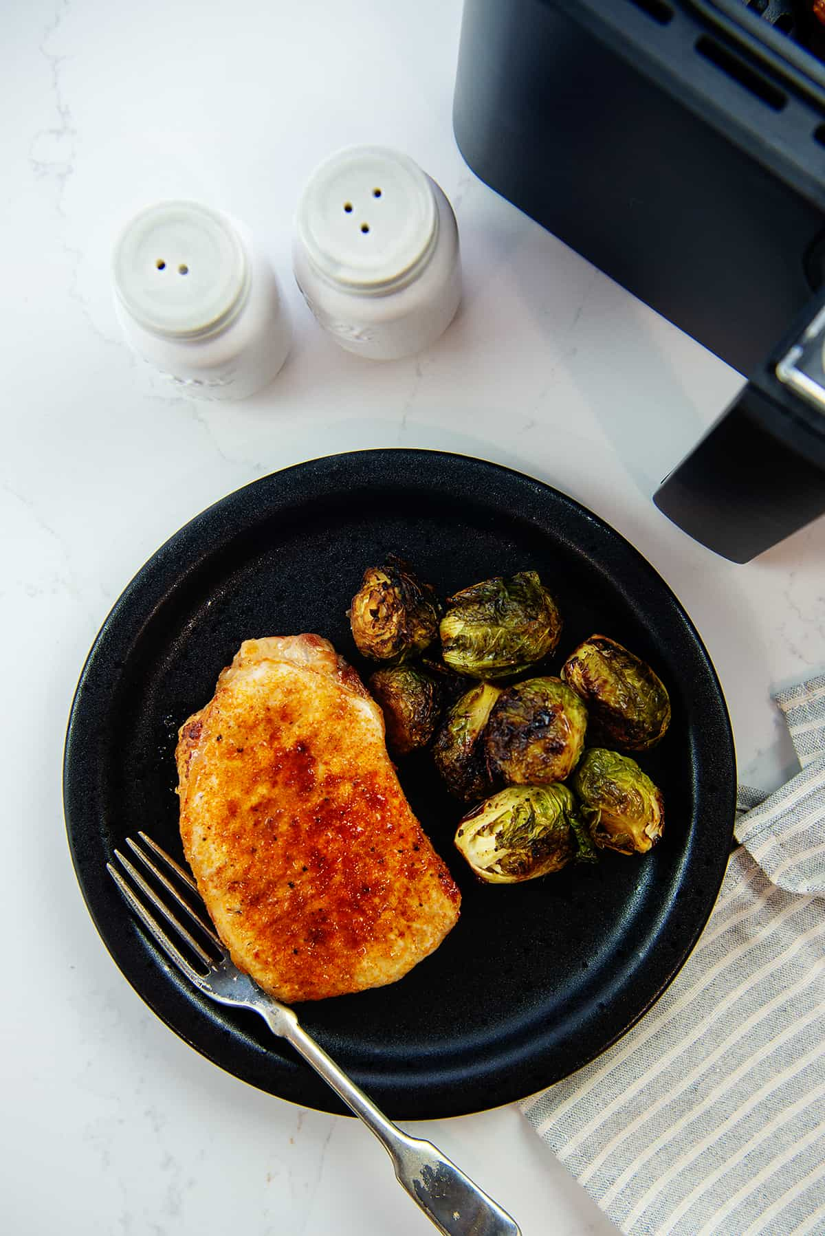 pork chop on plate with Brussels sprouts.