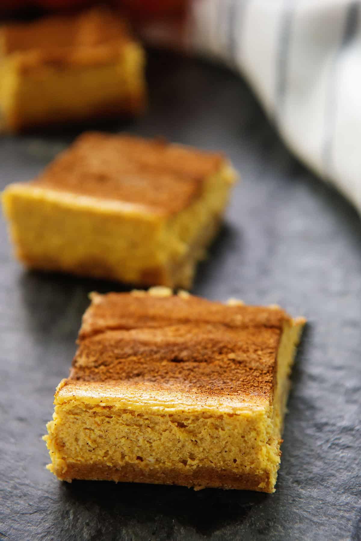 keto pumpkin cheesecake bars on black background.