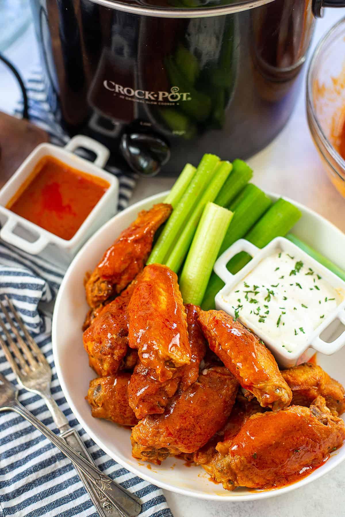 crockpot buffalo chicken wings piled in bowl.
