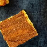 keto pumpkin cheesecake bar on slate surface.