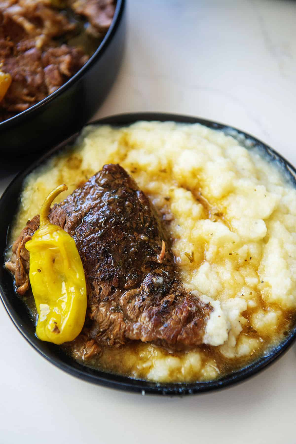 low carb Mississippi pot roast on black plate with cauliflower mash.