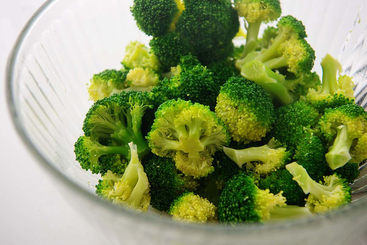 steamed broccoli in glass bowl.