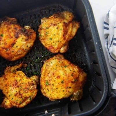 chicken thighs in air fryer basket.
